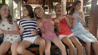 Diverse multi racial Asian and Caucasian group of six young happy smiling girls chair dancing and having fun together