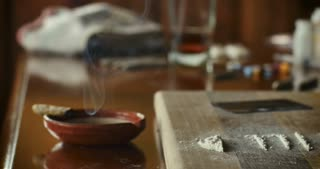 Dolly shot of a smoking marijuana joint with lines of white powder such as crushed oxycodone or cocaine, and other drugs in the background
