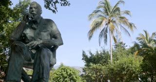 Dolly shot of John Huston statue in Isla Cuale park Puerto Vallarta, Mexico against a blue sky with mountains and a palm tree in the background