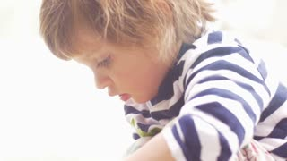 Dreamy moment of a cute little girl concentrating on playing in slow motion
