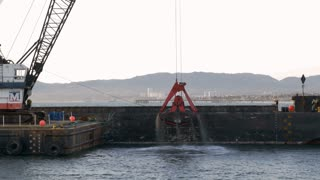Dredger ship digging sand out of ocean floor on to a barge