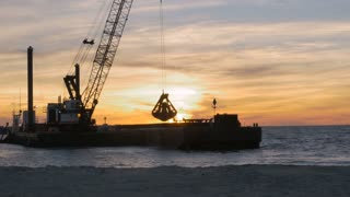 Dredger ship removing sand from ocean bottom at sunset to control beach erosion from climate change