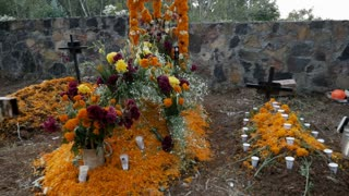 Elaborately decorated grave shrine and alter with fruit orange marigolds and other flowers for the Mexican holiday celebration of Day of the Dead