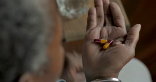 Elderly black woman in her 50s or 60s taking prescription pharmaceutical capsules drugs in her home - OTS