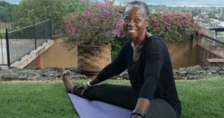 Elderly happy smiling active African American woman in 60s stretching her legs sitting on a yoga mat - dolly shot