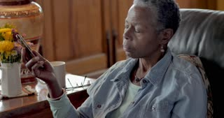 Elderly senior black woman in her 50s or 60s answering, talking on and hanging up a smart phone in her living room while sitting on a leather sofa