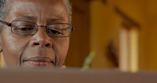 Elderly senior black woman in her 50s or 60s thinking and processing information while looking at a computer monitor - dolly shot