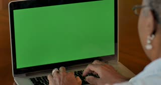 Elderly senior black woman in her 50s or 60s typing on laptop with a green screen chroma key background - OTS