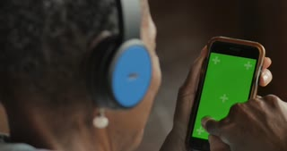 Elderly senior black woman selecting music from her green screen smart phone mobile app streaming service - OTS