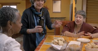 Elderly woman pouring wine for her mixed racial friends over 50 while they talk at a party
