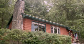 Establishing shot of a log cabin in the woods - locked down shot in the summer during the day