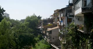 Establishing shot of many houses or apartments built on a hillside overlooking lush trees and a river