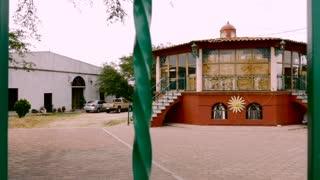 Establishing shot of round artisan Spanish style house or workshop behind green bars