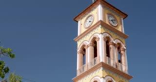 Establishing shot of the clock tower of the Parroquia de la Santa Cruz in Puerto Vallarta, Mexico against a clear blue sky