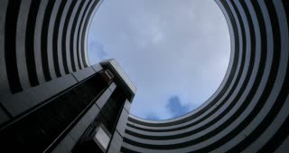 Establishing shot of the sky rotating through the opening of a round futuristic skyscraper or apartment building