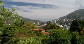 Establishing shot pan of houses and apartments built on a lush mountain forest or jungle in a tropical climate