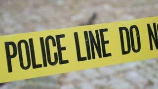 Exterior crime scene tape outside daytime Police Line Do Not Cross dolly shot