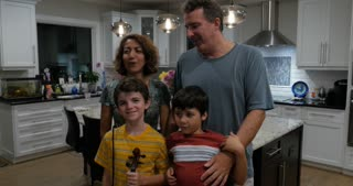Family posing for a photograph portrait in their modern kitchen with two pre teenage brothers one who is dancing around and misbehaving