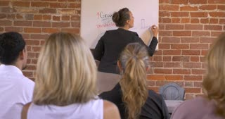 Female multi-ethnic motivational speaker getting the audience excited at a business presentation writing on a dry erase board