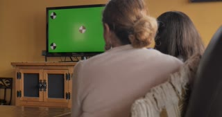 Female parent and daughter watching a green screen television together - dolly shot