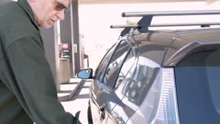 Fit active senior man closes his gas cap at a gas station and gets into the driver side of his car