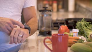Fit man looking at and tapping his smart watch in the morning in his kitchen - slow motion