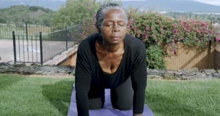 Flexible healthy retired African American woman in her 60s doing cat cow yoga pose on an exercise mat