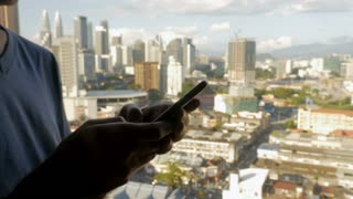 Fly over a man typing on his mobile cell phone overlooking a modern downtown city with large skyscrapers in slow motion