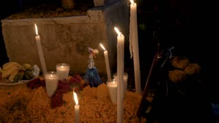 Fresh fruit used as an offering, a Katrina figurine, and candles on top of a grave during day of the dead in Mexico - dolly shot