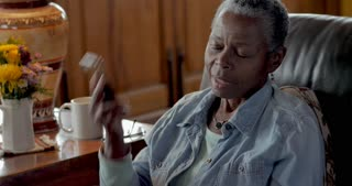 Frustrated, mad, senior black woman in her 50s or 60s talking on her mobile phone displeased at the annoying caller on the other end