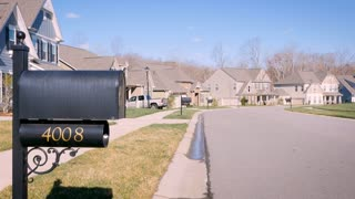 Generic suburban neighborhood during the winter day with a mailbox and bare trees blowing in the wind establishing shot