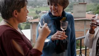 Group of three diverse attractive mature women in their 60s talking and drinking wine outside on a balcony in slow motion