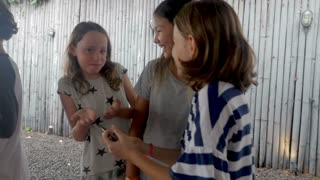 Group of three multi ethnic young girls age 11 - 12 sharing technology and telling stories while holding a smart phone and acting surprised in slow motion