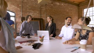 Group of young diverse creative designers at a meeting laughing and celebrating a successful business in slow motion