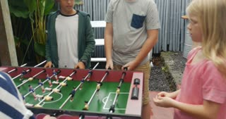 Group of young pre teen friends with both boys and girls playing foosball together and having fun