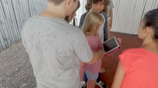 Group of young pre teenage children watching a video or app on a digital tablet together in slow motion