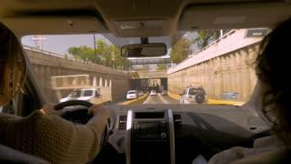 GUADALAJARA, MEXICO - CIRCA FEB 2017 - Woman and man driving an SUV car under an underpass in Santa Maria del Pueblito, Zapopan Jalisco, Mexico