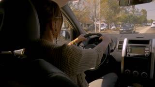 GUADALAJARA, MEXICO - CIRCA FEB 2017 - Woman driving an SUV on Calzada Lazaro Cardenas during the day through moderate traffic while a male passenger navigates using a digital map program on his phone