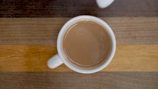 Hand adding a teaspoon of sugar to a cup of tea or coffee with milk - overhead slow motion shot