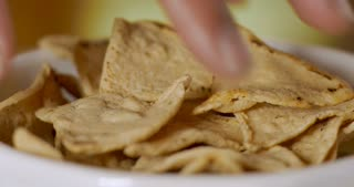 Hand grabs a handful of corn tortilla chips from a bowl - close up