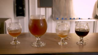 Hand reaches in to pickup a snifter of robust craft beer and puts it back while lined up next to small tasting snifters of different varieties of beers at a brewpub or brewery