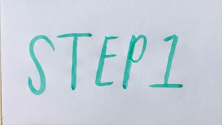 Hand writes STEP 1 in block letters with a green brush pen on white paper - handwriting typography close up