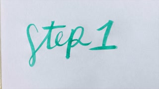 Hand writes STEP 1 in cursive with a green brush pen on white paper - close up handwriting typography