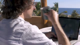 Handsome digital nomad freelance man drinks coffee while working outside home office with ocean view on laptop computer