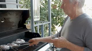 Handsome elderly senior man in his 70s holding a glass of red wine grilling potatoes on a gas bbq in slow motion