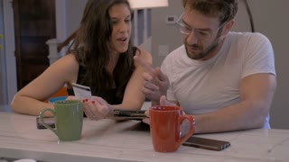 Handsome man and beautiful woman in early 30s shopping online together in their home on a digital tablet checking out their purchase with a credit card or debit card - slow motion
