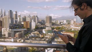 Handsome man responding to messages and notifications on his smart phone outside overlooking a large city with the Petronas Towers and the Exchange 106 in view in Kuala Lumpur, Malaysia