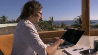 Handsome man telecommuting on laptop computer working at his home office overlooking the beach push in slow motion