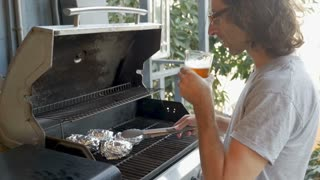 Handsome man with long hair drinking a craft beer turning baked potatoes on a bbq grill with metal tongs in slow motion