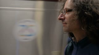 Handsome man with long hair standing on a subway platform as the metro train goes by in slow motion